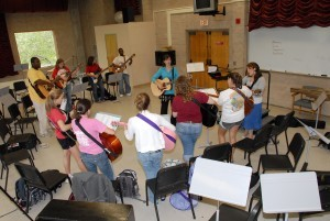 members of a music therapy class standing in a circle, playing guitar
